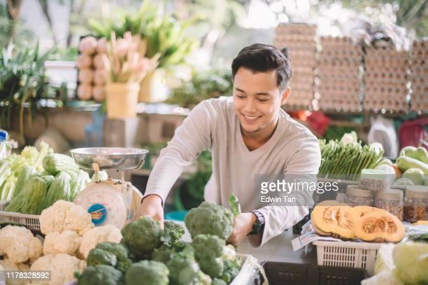 アジアのマレー系野菜小売オーナーが野菜を手配してビジネスの準備をする - ファーマーズマーケット ストックフォトと画像