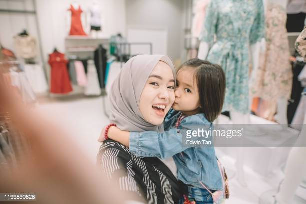 an asian malay young woman shopping in a boutique shop with her daughter taking selfie