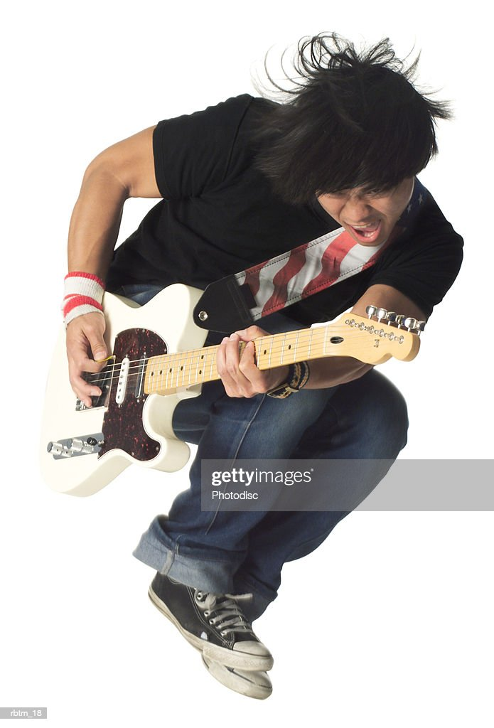 an asian male teen in jeans and a black shirt jumps up while playing an electric guitar : Foto de stock