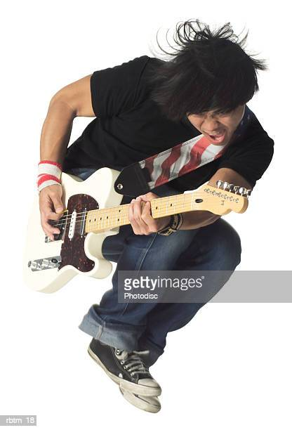 an asian male teen in jeans and a black shirt jumps up while playing an electric guitar