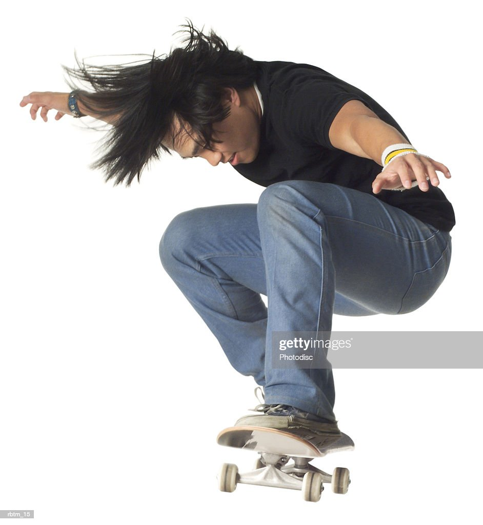 an asian male teen in jeans and a black shirt jumps up while riding a skateboard : Foto de stock