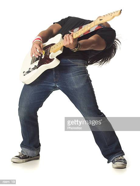 an asian male teen in jeans and a black shirt leans back while playing an electric guitar