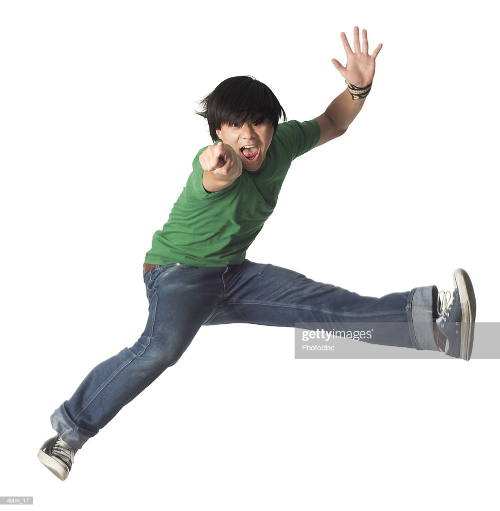 an asian male teen in jeans and a green shirt jumps up and points forward : Foto de stock