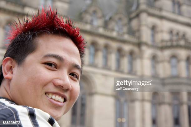 An Asian male with red dyed hair watching the Chinese dragon dance at the Manchester Food and Drink Festival