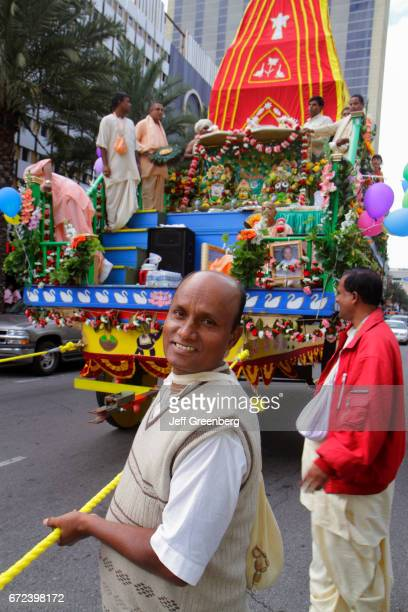 An Asian man pulling a decorated chariot at the Festival of India