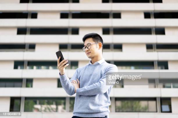 an asian man using mobile phone in downtown district - borough district type stock pictures, royalty-free photos & images