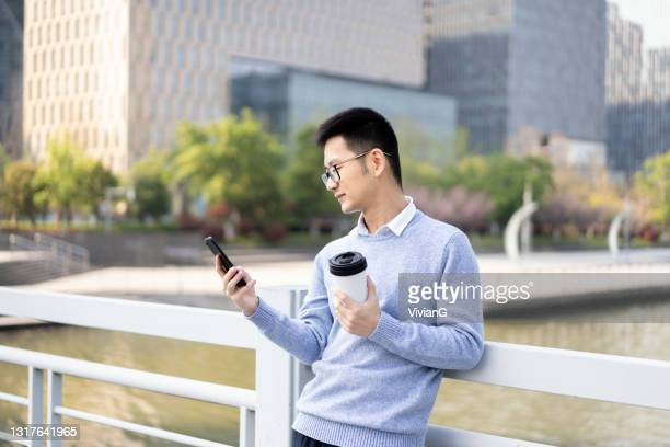 an asian man using mobile phone with coffee in downtown district - borough district type stock pictures, royalty-free photos & images