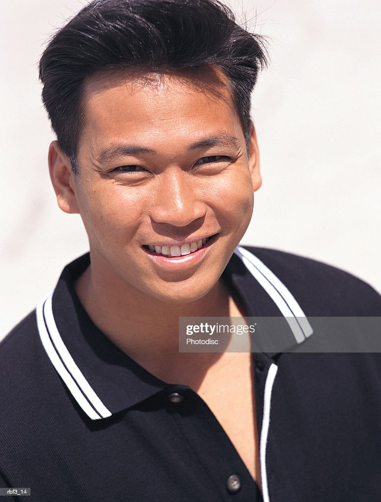 an oriental man wearing a black shirt smiles as he squints in the bright sunlight : Stockfoto