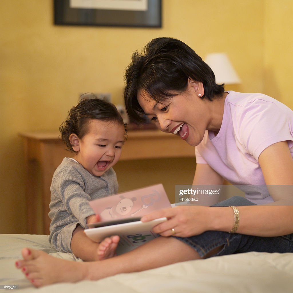 an asian mother shows a book to her toddler son : Stockfoto