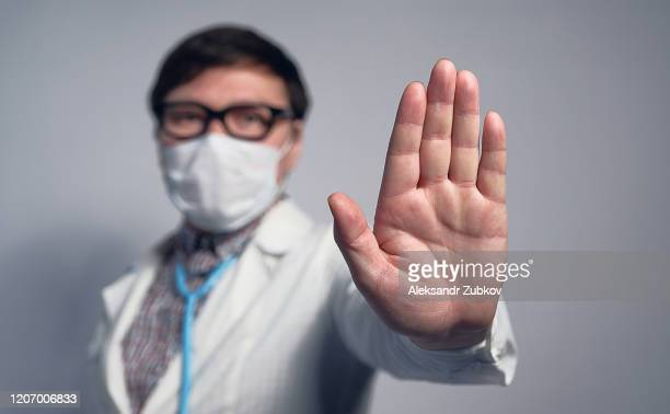 an asian or chinese doctor in a medical mask and glasses shows a warning stop sign with his hand. - ストップ ストックフォトと画像