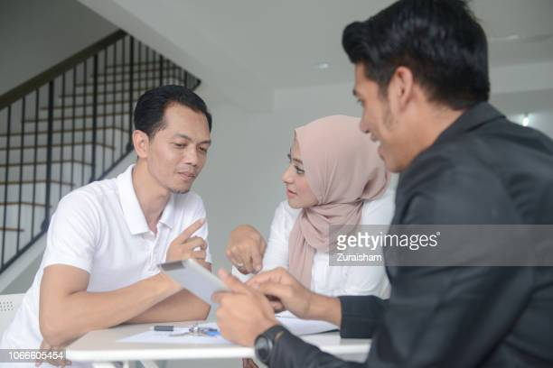 an asian real estate agent and happy young muslim couple discussing on their new home - real estate developer stock pictures, royalty-free photos & images