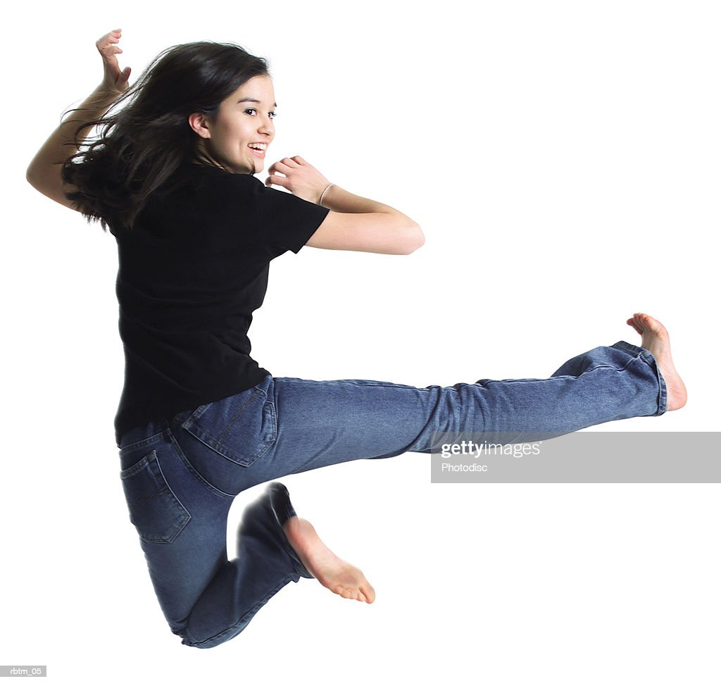an asian teenage girl in jeans and a black shirt kicks and jups through the air : Foto de stock