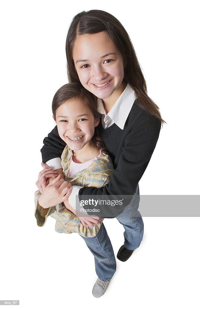 an asian teenage girl in jeans and a black sweater wraps her arms around her little sister and smiles up into the camera : Foto de stock