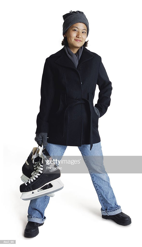 an asian teenage girl wearing a winter coat and hat is holding her ice skates and standing spread legged : Foto de stock