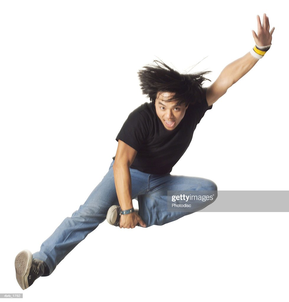 an asian teenage male in jeans and a black shirt jumps up wildly through the air : Stockfoto
