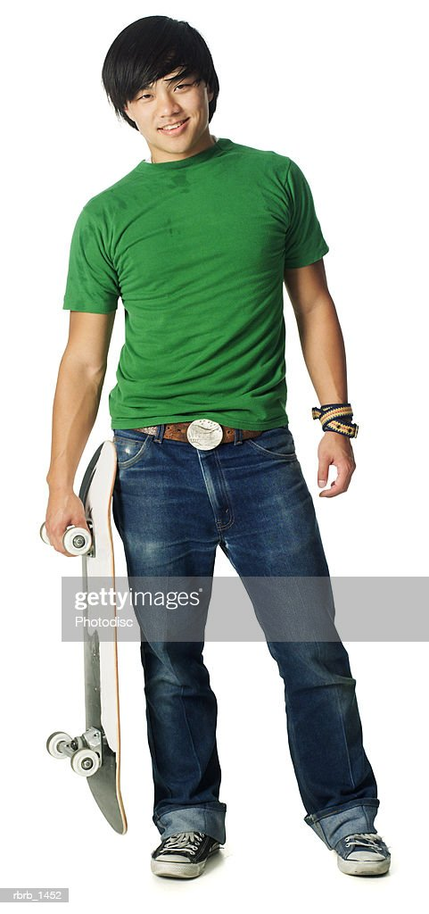 an asian teenage male in jeans and a green shirt smiles as he holds his skateboard : Stockfoto