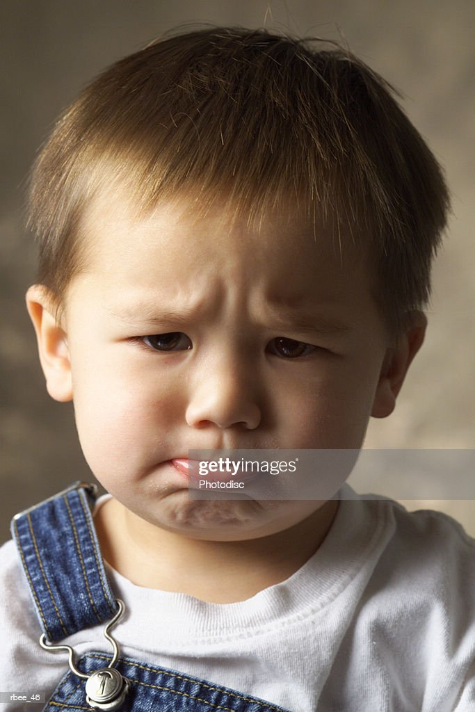 an asian toddler boy in overalls scrunches his eyebrows and sticks out his lower lip in a pout : Stockfoto