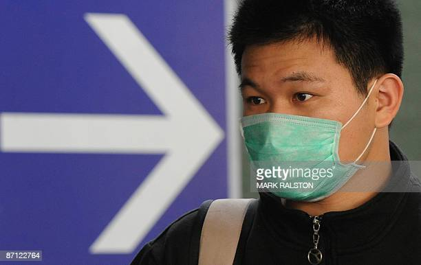 An Asian traveller wears a face mask to protect himself against Swine Flu as he arrives at Los Angeles International Airport on May 11 2009 The swine...
