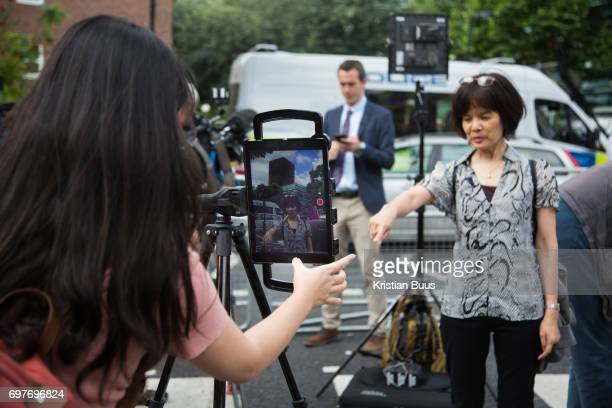 An Asian tv station get ready to broadcast using an iPad below the burned out tower June 16th 2017 London United Kingdom Grenfell Tower burned out...