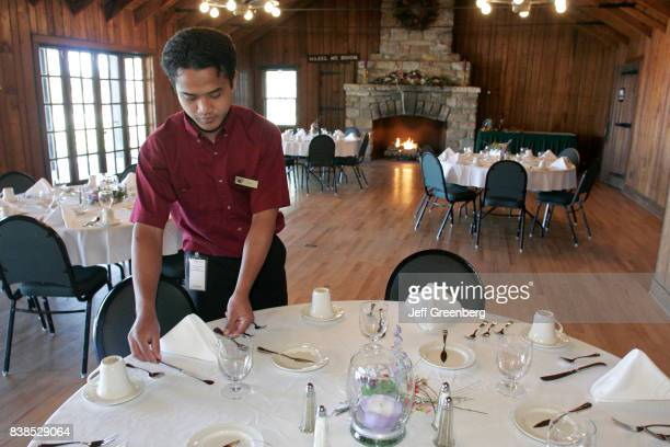 An Asian waiter setting the banquet tables inside the Conference Hall at Skyland Resort.