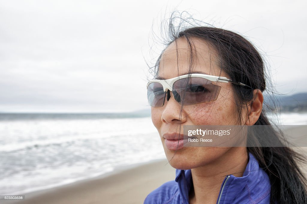An Asian woman athlete wearing sunglasses on the beach, looking away : Stock Photo