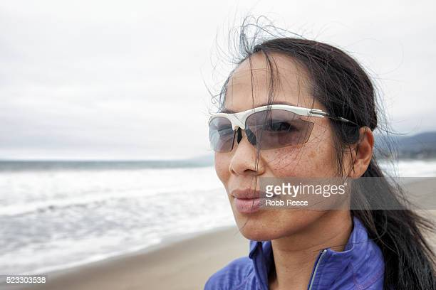 an asian woman athlete wearing sunglasses on the beach, looking away - robb reece imagens e fotografias de stock