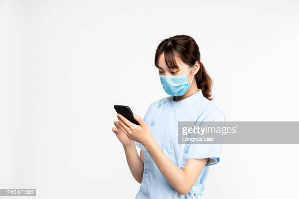 an asian woman doctor wearing a mask is using the phone - three quarter length stock pictures, royalty-free photos & images