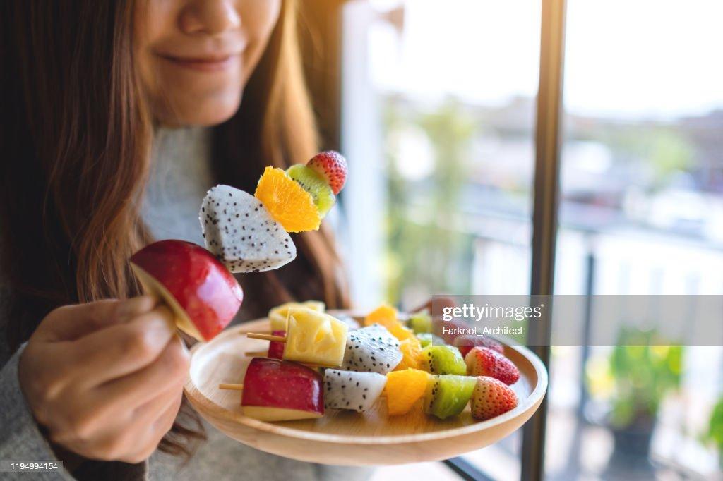 een Aziatische vrouw die een vers gemengd fruit op spiesjes houdt en eet : Stockfoto