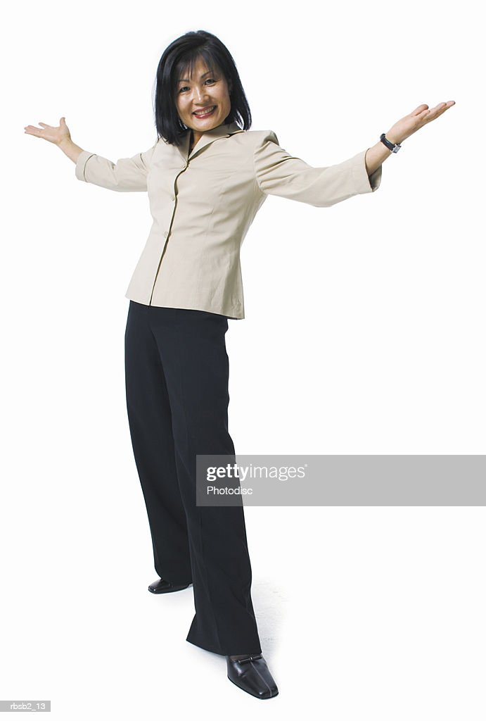 an asian woman in black pants and a tan blouse holds her arms out and smiles : Foto de stock