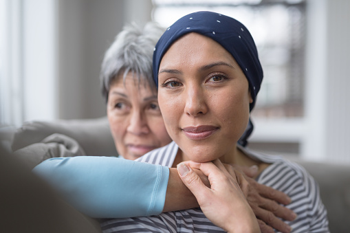 An Asian woman in her 60s embraces her mid-30s daughter who is battling cancer 1044548366