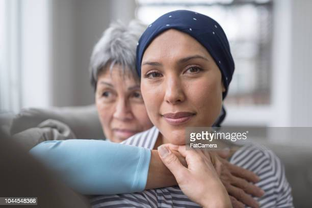 an asian woman in her 60s embraces her mid-30s daughter who is battling cancer - ethnicity stock pictures, royalty-free photos & images