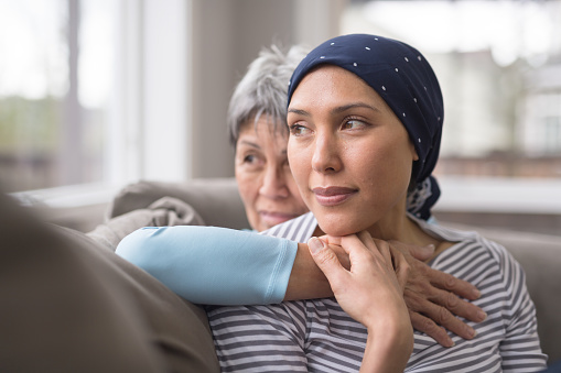 An Asian woman in her 60s embraces her mid-30s daughter who is battling cancer 962659624
