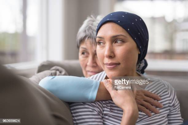 an asian woman in her 60s embraces her mid-30s daughter who is battling cancer - sostegno morale foto e immagini stock