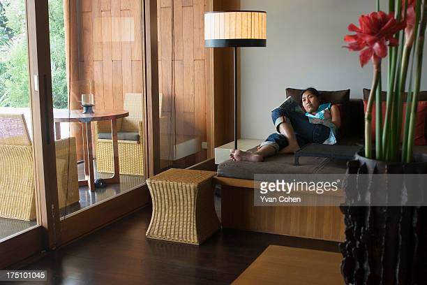 An Asian woman relaxes reading a book in one of the rooms of the Chedi Hotel in Chiang Mai A part of the GHM Group the Chedi Hotel provides its...