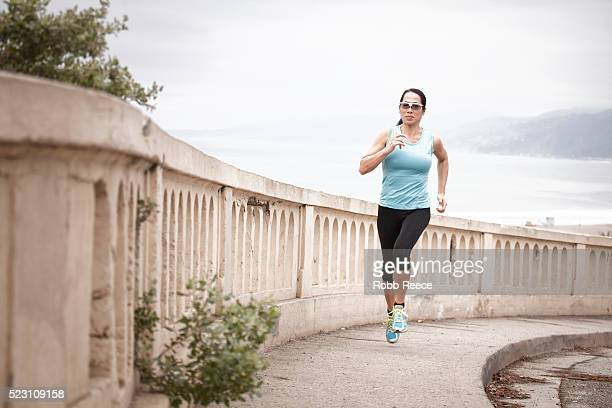 an asian woman running uphill for exercise along a sidewalk with the beach behind her - robb reece 個照片及圖片檔
