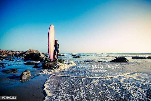 an asian woman surfer stands with her surfboard looking out to the ocean in california at sunset - robb reece 個照片及圖片檔