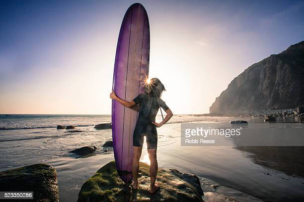 an asian woman surfer stands with her surfboard looking out to the ocean in california at sunset - robb reece stockfoto's en -beelden