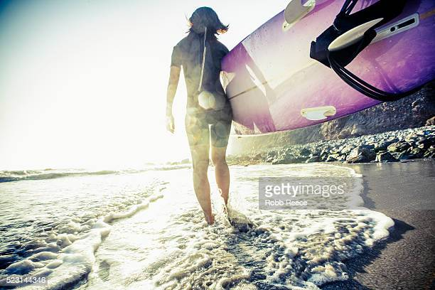 an asian woman surfer walks on the beach with her surfboard in california at sunset - robb reece bildbanksfoton och bilder