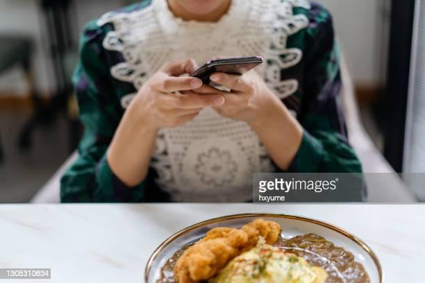 une femme asiatique prenant la photo de son riz japonais de curry de katsu - yōshoku photos et images de collection