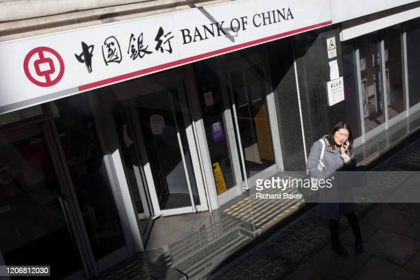An Asian woman using her mobile phone stands outside the Shaftesbury Avenue branch of the Bank of China in London's West End, on 12th March 2020, in...