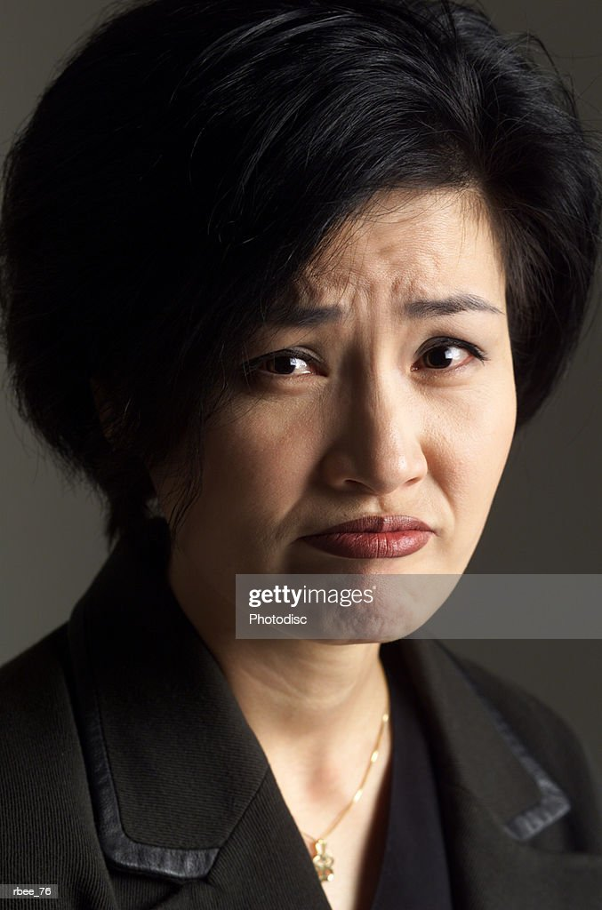 an asian woman wearing a dark suit has short hair and is frowning in an expression of sadness : Stockfoto