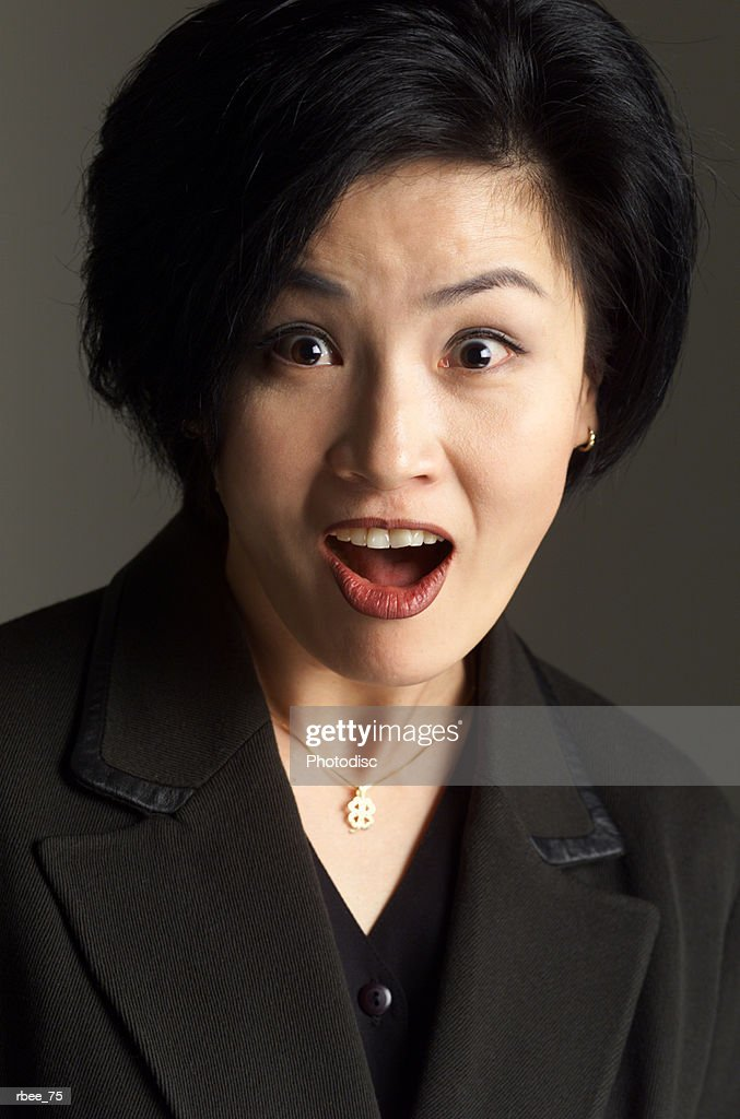an asian woman wearing a dark suit has short hair and is staring open mouthed with an expression of shock : Stockfoto