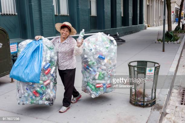An Asian woman with bags of recycling aluminum cans.
