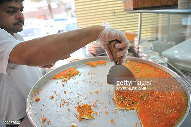 An Asian worker serves 'Kenafa' a local desert popular during iftar meals after breaking the day's fast during the holy Muslim month of Ramadan at a...