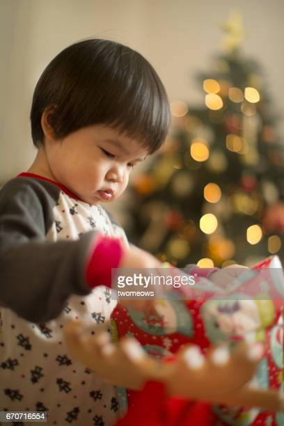 An asian young child unwrapping a Christmas gift.
