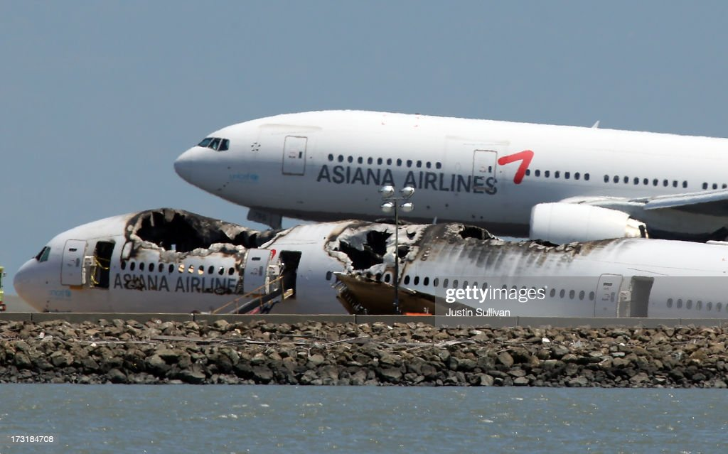 An Asiana Airlines flight lands next to the wreckage of Asiana Airlines flight 214 as it sits on runway 28L at San Francisco International Airport on July 9, 2013 in San Francisco, California. Three days after Asiana Airlines flight 214 crash landed at San Francisco International Airport, the National Transportation Safety Board (NTSB) is continuing their investigation as to why the plane crashed.