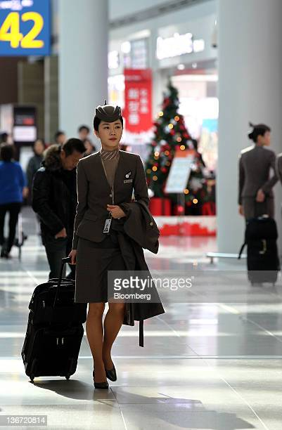 An Asiana Airlines Inc flight attendant walks through the duty free shopping area at Incheon International Airport in Incheon South Korea on Tuesday...