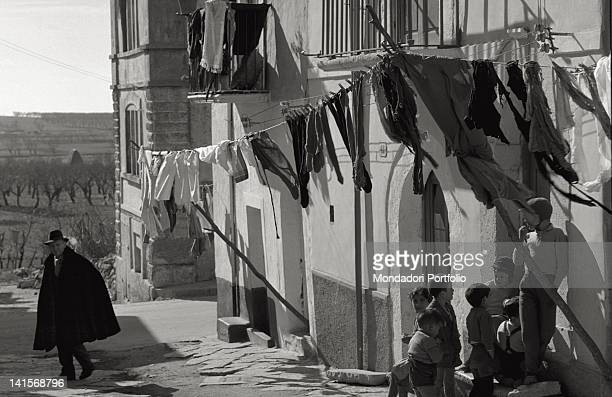 An aspect of life in San Giovanni Rotondo man wearing a heavy overcoat children playing on the street and washing hanging out to dry Italy