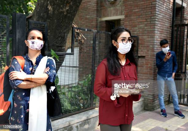An aspirant along with her mother fills an admission form on her mobile phone after Delhi University's First Cut Off List 2020 released, at North...
