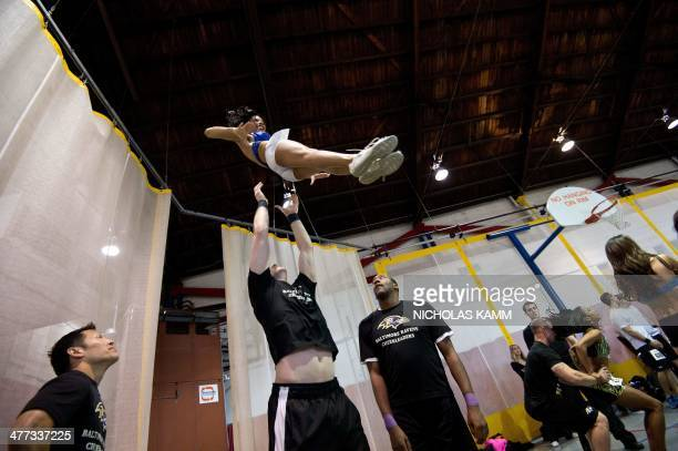 An aspiring cheerleader practices a stunt during the first day of the Baltimore Ravens tryouts at a gym in Batimore Maryland on March 8 2014 The...